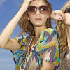 Portrait of two beautiful blonde and brunette girl in sunglasses on background blue sky