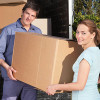 Portrait of couple carrying cardboard box while moving into new home